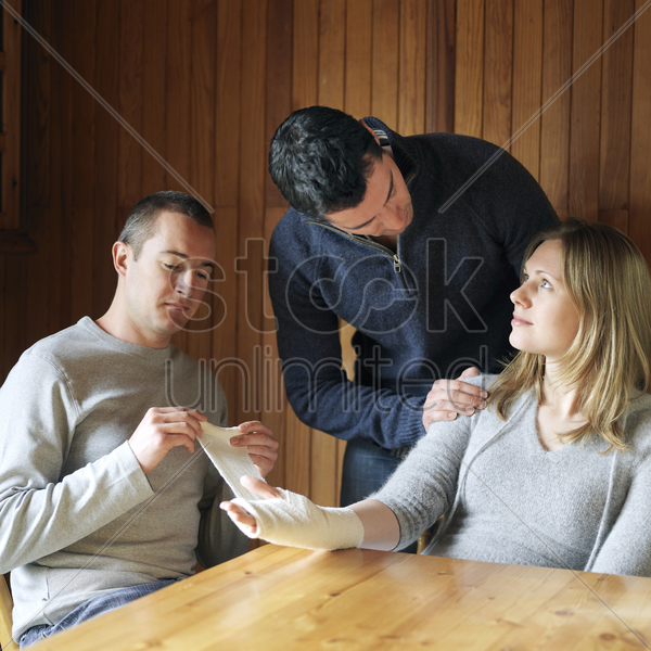 man wrapping woman's injured palm stock photo