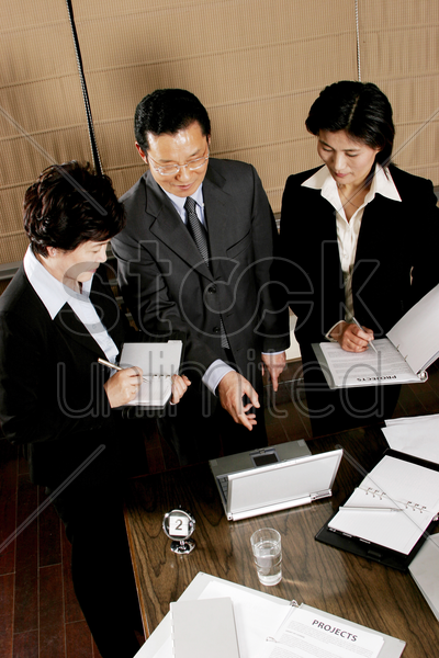 manager showing some information on his laptop to his assistants stock photo