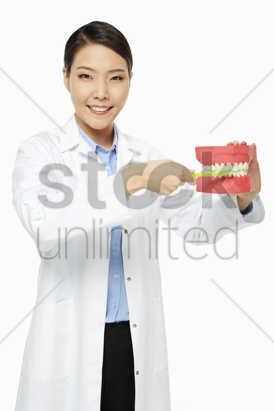 medical personnel demonstrating how to brush teeth stock photo