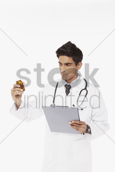 medical personnel examining a bottle of pills stock photo