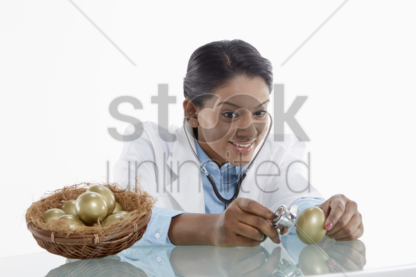 medical personnel examining a golden egg stock photo