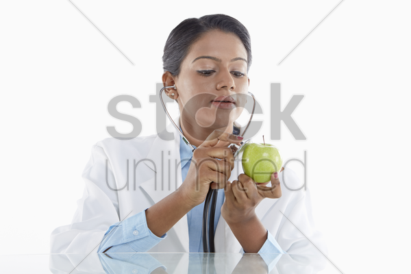 medical personnel examining a green apple stock photo
