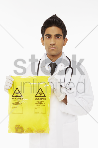 medical personnel holding a bag of biohazard waste stock photo