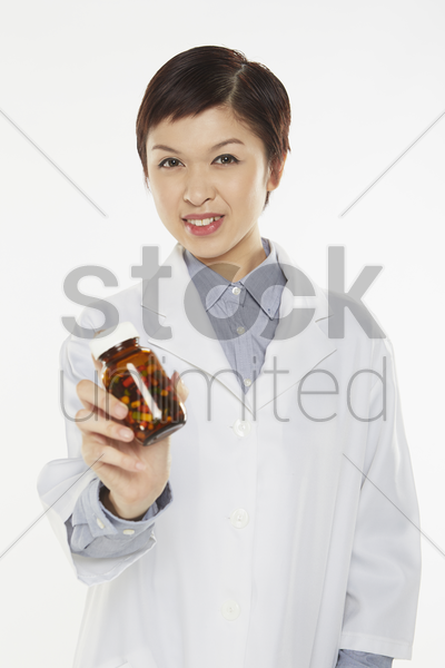 medical personnel holding a bottle of pills stock photo