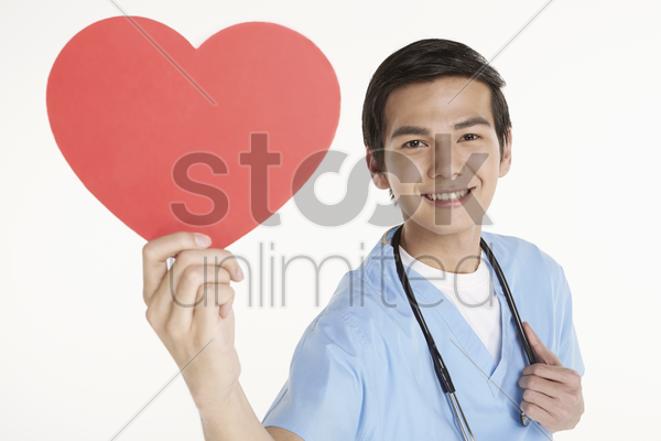 medical personnel holding a cut out heart shape stock photo
