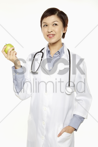 medical personnel holding a green apple stock photo