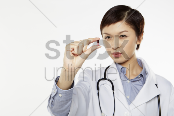 medical personnel holding a single pill stock photo