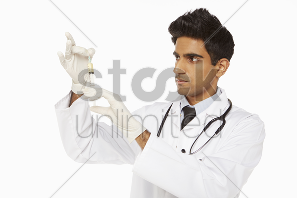 medical personnel holding a syringe stock photo