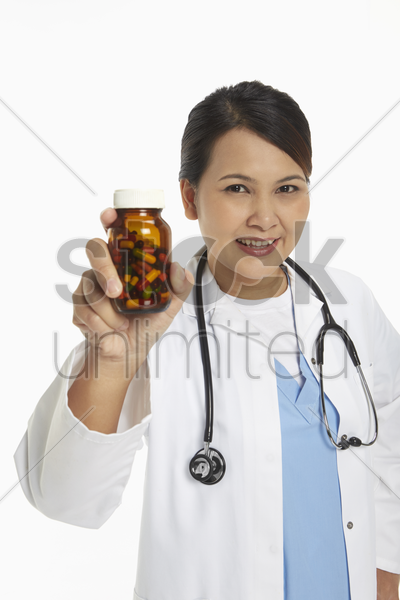 medical personnel holding up a bottle of pills stock photo