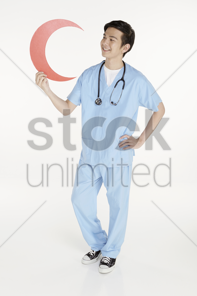 medical personnel holding up a cut out red crescent sign stock photo