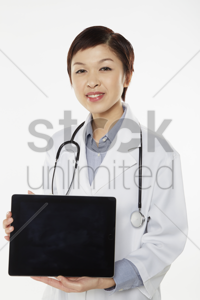 medical personnel holding up a digital tablet stock photo