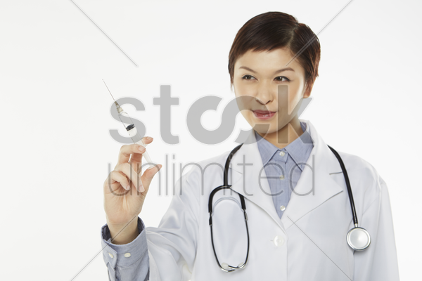 medical personnel holding up a syringe stock photo