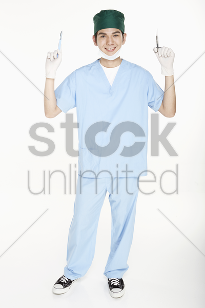 medical personnel holding up surgical equipment stock photo