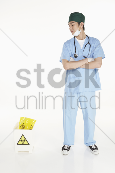 medical personnel looking at the biohazard waste bin stock photo
