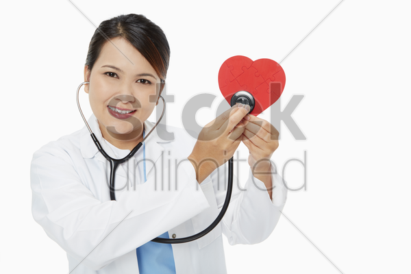 medical personnel placing a stethoscope against a red heart stock photo