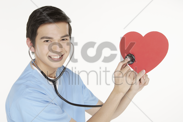 medical personnel placing stethoscope on cut out heart shape stock photo
