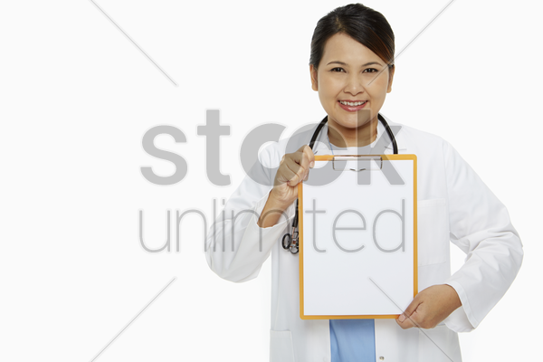 medical personnel smiling and holding up a blank clipboard stock photo