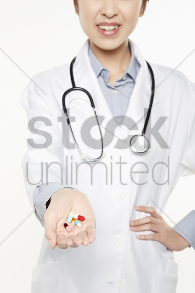 medical personnel with pills in her hands stock photo