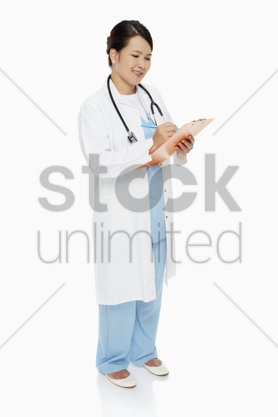 medical personnel writing down notes on clip board stock photo
