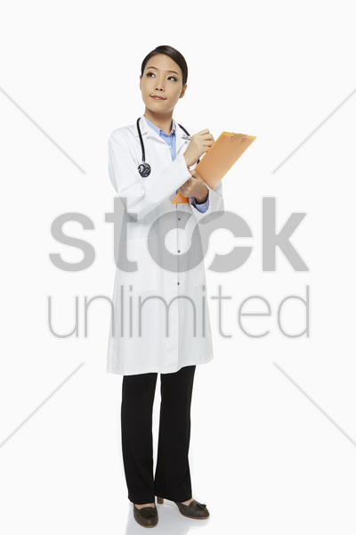 medical personnel writing notes on a clipboard stock photo