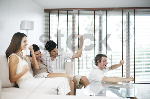 men and women cheering while watching television at home stock photo