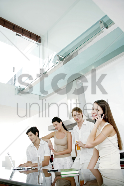 men and women hanging out in the kitchen stock photo