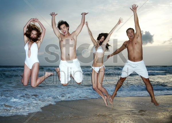 men and women jumping happily on the beach stock photo