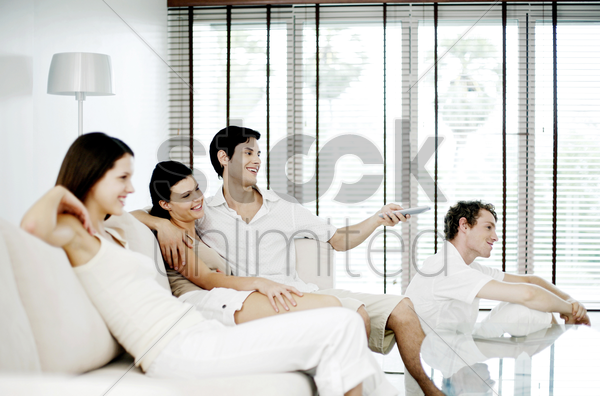 men and women watching television at home stock photo