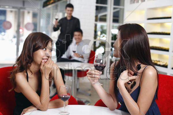 men flirting with women sitting at another table stock photo