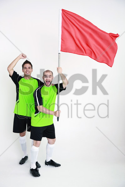 men in football jerseys with one holding a red flag stock photo