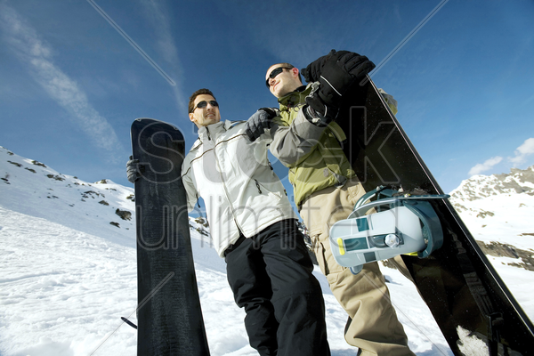 men posing with their snowboards stock photo