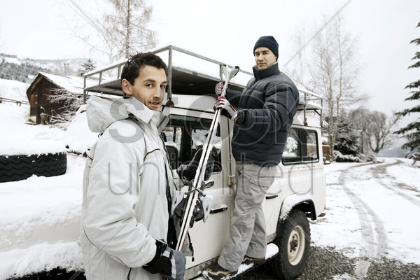 men taking out skis from the jeep stock photo