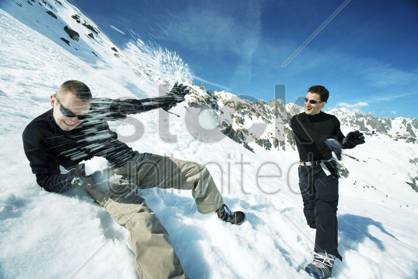 men throwing snowballs at each other stock photo
