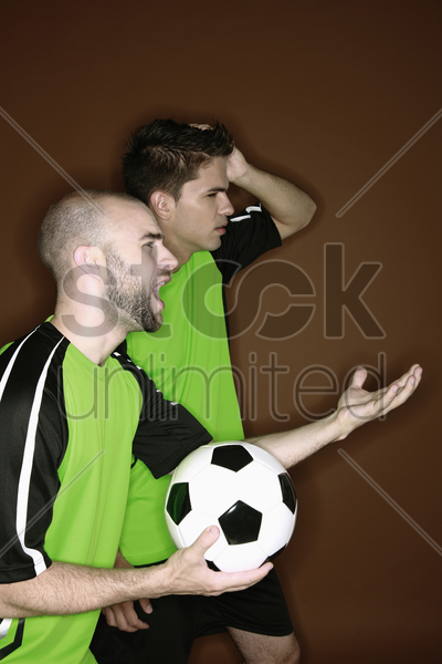 men touching their heads with disappointment while watching football match stock photo