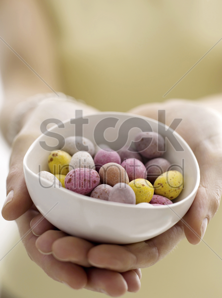 mini eggs in bowl with model stock photo