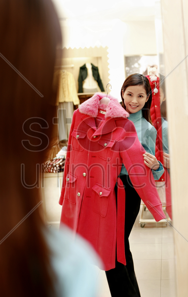 mirror reflection of a woman trying out a trench coat stock photo