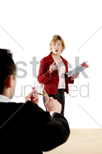 mischievous boy trying to shoot his teacher with a slingshot stock photo