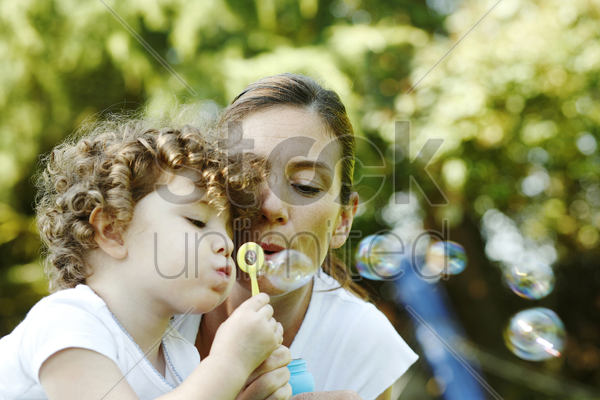 mother and daughter blowing out soap bubbles together stock photo