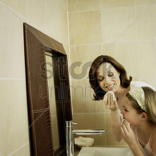 mother and daughter cleaning face with facial cotton stock photo