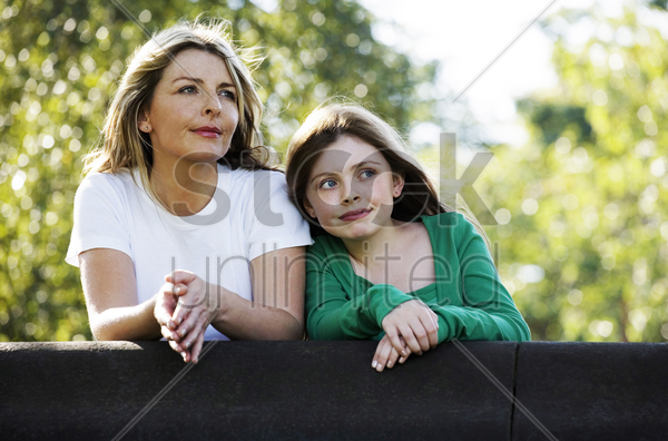mother and daughter enjoying the beautiful scenery of the park stock photo