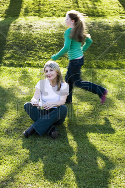 mother and daughter having fun in the park stock photo