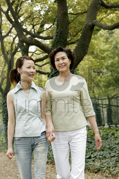 mother and daughter holding hands while walking in the park stock photo