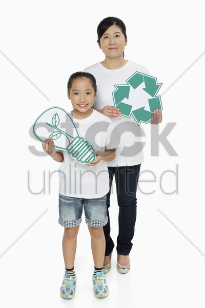 mother and daughter holding up a recycle logo as well as a cut out light bulb stock photo
