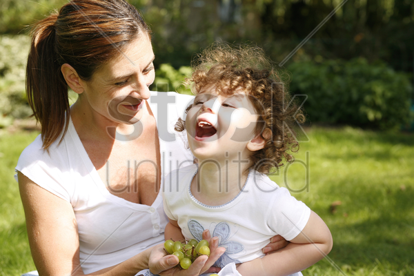 mother and daughter picnicking in the park stock photo