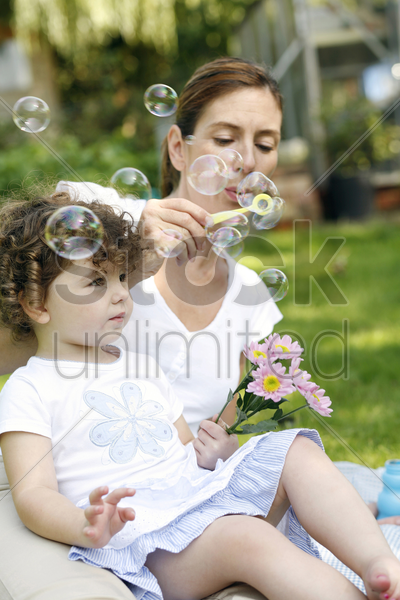 mother and daughter playing with soap bubbles in the park stock photo