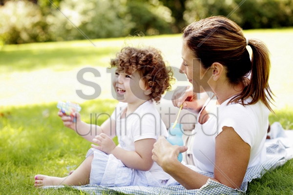 mother and daughter playing with soap bubbles stock photo