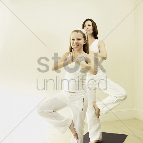 mother and daughter practicing yoga stock photo