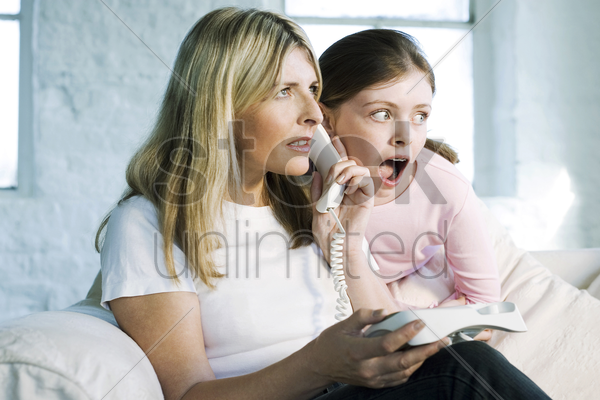 mother and daughter receiving shocking news stock photo