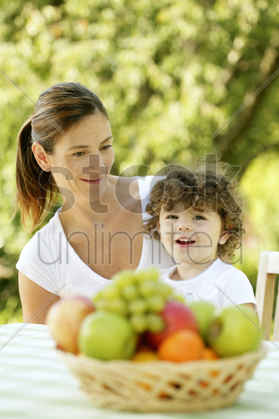 mother and daughter sitting at the picnic table stock photo