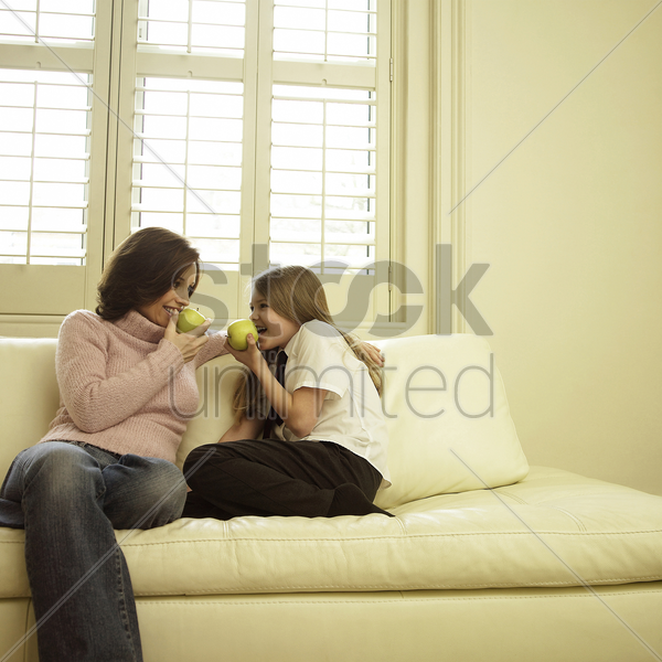 mother and daughter sitting on the couch eating green apples stock photo